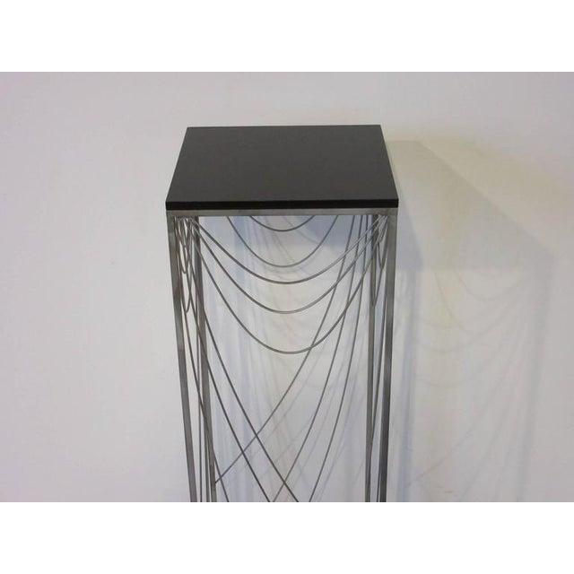 A light wispy spider web swag styled Jere pedestal with satin black wood top and sculptural steel frame design. Makes a...