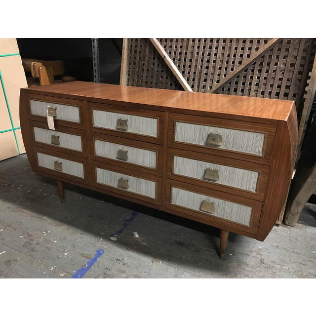 Wooden chest of drawers with white paneling centered on each drawer, curved sides.