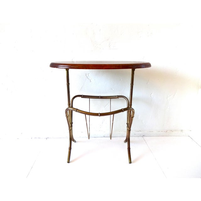 A vintage, mid-century modern side table with a beveled oval wood top and a faux bamboo, brass frame with incorporated...
