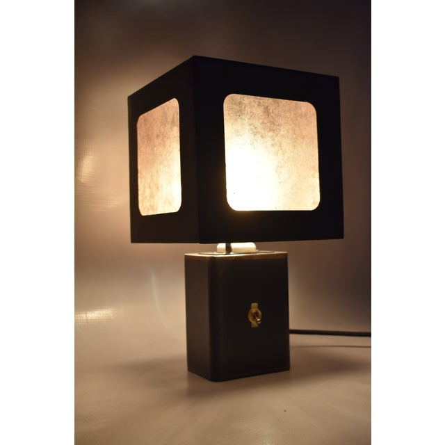 Blackened steel table lamp with grey mica paneling. Antique black patina finish with bronze accents. The idea for this...