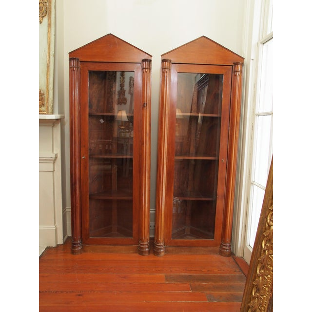 A pair of fruitwood corner cabinets with simple, unadorned pediments over glazed doors flanked by slender, fluted columns....