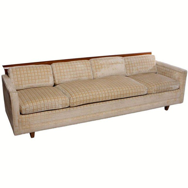 Tuxedo sofa with architecturally curved walnut wood across the top back. Walnut legs and creamy beige crosshatch cut...