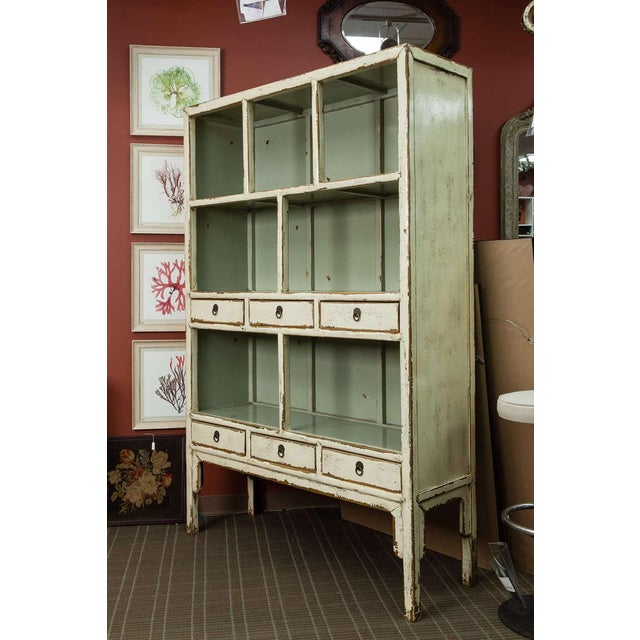 Circa 1900s Chinese cabinet has a cream color lacquer finish on the outside with a contrasting celadon interior. The top...