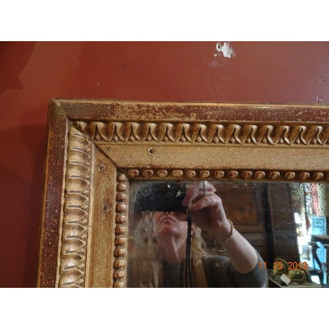 Simple , elegant 19th Century French gilt wood mirror. Bead pearl motif inside frame and stylized carving all around.
