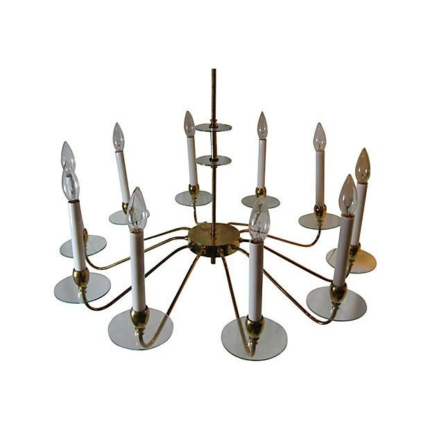 An elegant 10 arm brass and glass chandelier in the style of Fontana Arte. The chandelier has glass bobeches, arms, and...