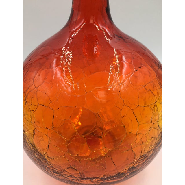 Tangerine crackle ball decanter #654 designed by Joel Myers for the Blenko Glass Co. of Milton, West Virginia. The piece...