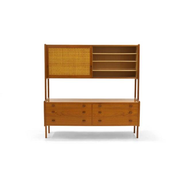 Excellent original condition Hans Wegner storage cabinet in teak. Sliding cane covered teak sliding doors on top reveal...