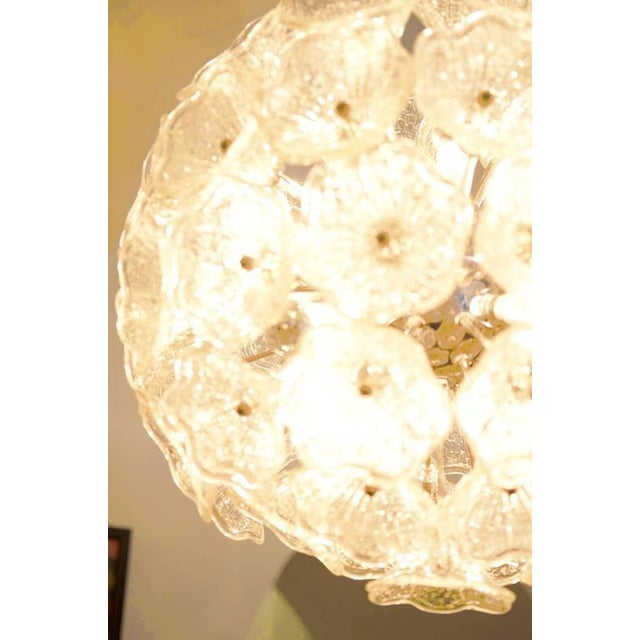 - Sputnik chandelier produced in the 1960s - Features a brass frame with clear handblown Murano glass flowers - Design is...