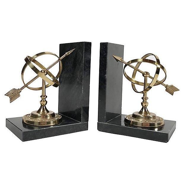 Pair of brass armillary spheres seated on solid black marble bases.