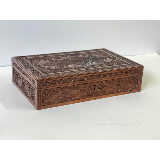 Early 20th century Anglo Raj wooden hand-carved jewelry box richly decorated overall with paisley and floral carvings. A...