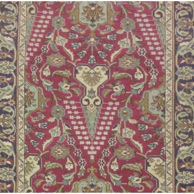 This beautiful rug is hand made, made in Iran. It features a pattern in a vibrant combination of red, navy, blue, white....