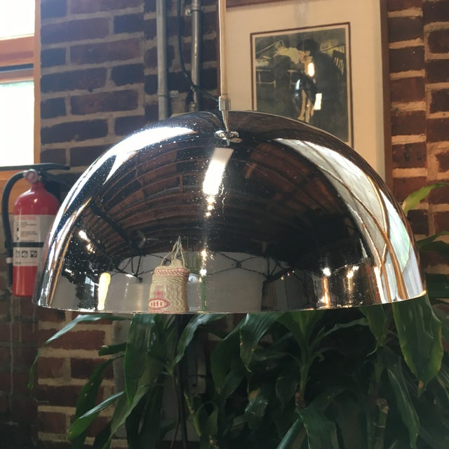 "Mid-century chrome pendant light made by Lightolier. The actual light measures 14"" in diameter and 6"" high. The total drop..."
