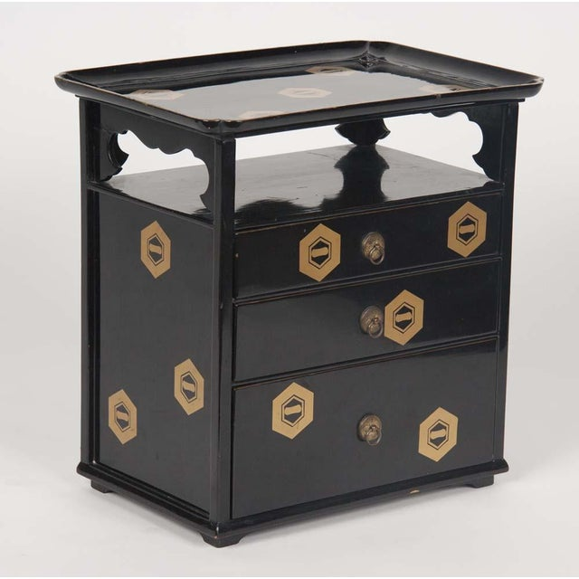 A Japanese, black lacquer cosmetics cabinet with a rectangular tray top over an open shelf and three drawers. Black...
