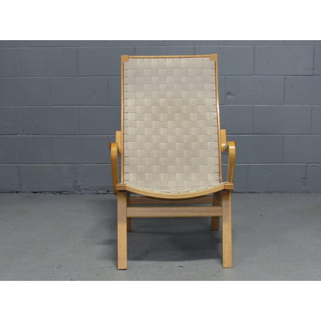 Designed by Finn Østergaard, this pair of beech-framed chairs support webbing on the seat and back.