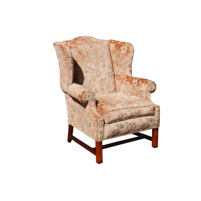 A pair of Chippendale style wingback chairs. Upholstered throughout in a blush colored floral velvet jacquard. Straight,...