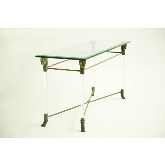 Solid brass Ram heads support .75 in.thick beveled glass, hoved feet detailed legs with crisscross support connecting...