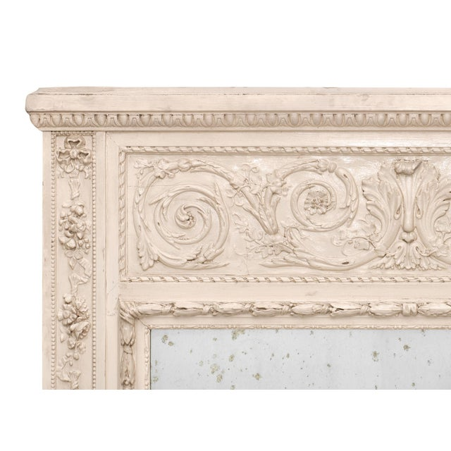 A French antique trumeau with hand carved details and a painted and patinated finish. This piece features the original...
