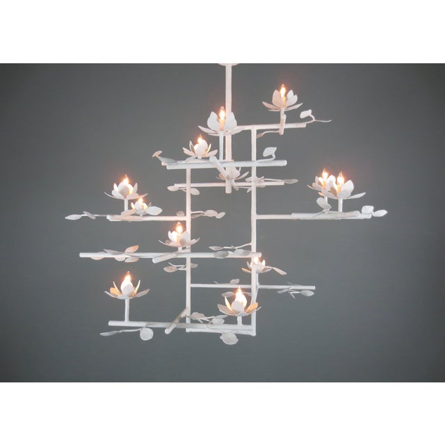 lotus flowers extend from non-centralized double poles. Plaster and steel multi armed chandelier with a white enamel...