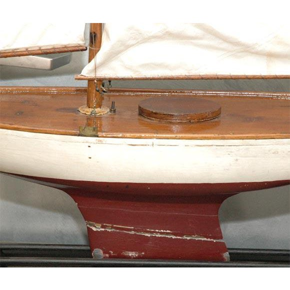 This wonderful early 20th century piece is one of the larger ponds boats we have seen. It has two sails and is painted...