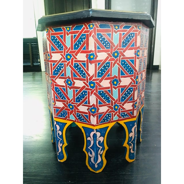 This is a hand-crafted Moroccan octagonal-shaped side table, lovingly hand-painted in a bright blue, red, yellow and pink...