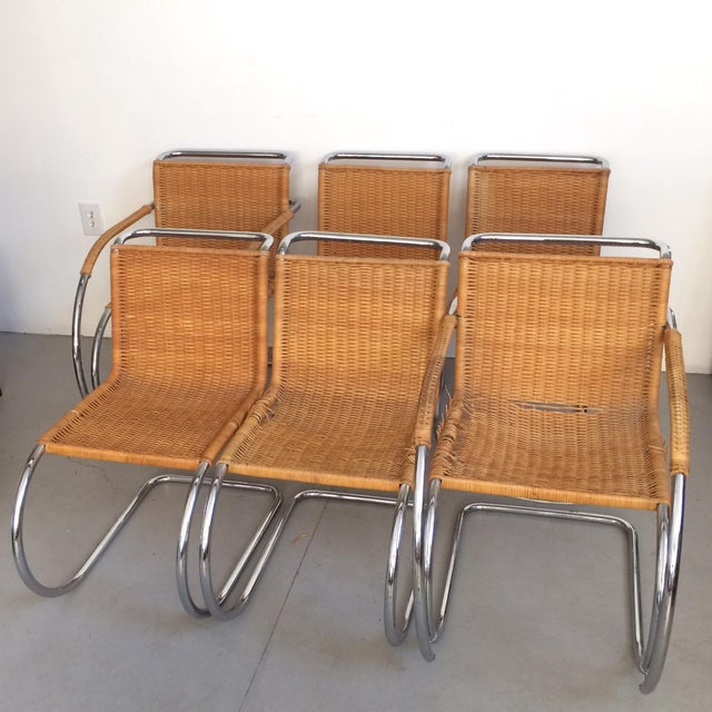 An original set of classic tubular chrome construction chairs with cane seat and back. Four MR10 armless chairs designed...