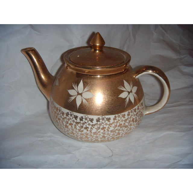 A very beautiful china teapot in white with gold decorations. A great decor item.