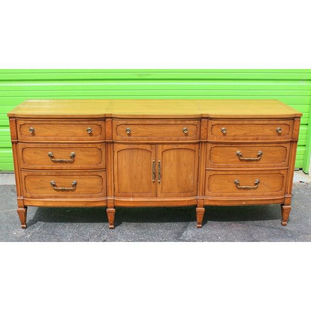 Mid-century walnut dresser with 7-drawer and double door storage space, beautiful brass hardware. Minor wear.