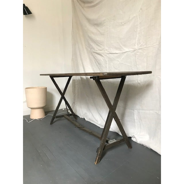 Foldable French antique wood table. Made in the early 20th century.