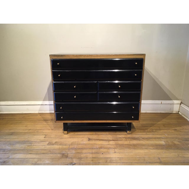 Cabinet in gloss black with hand-painted gold accents and original brass hardware. The cabinet has three drawers and It is...