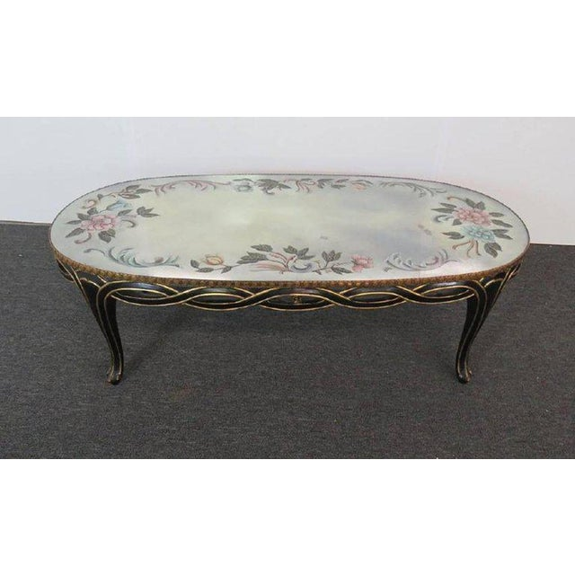 Jansen style eglomisé coffee table with floral paint decor and a gilt trim base.
