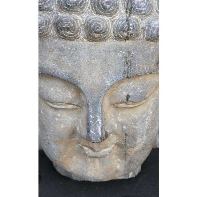 Monumental sandstone Buddha mounted on steel base.