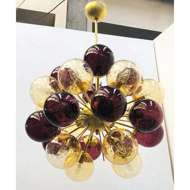 Italian chandelier shown in 24 amethyst and amber Murano glass globes with carefully blown bubbles within the glass using...