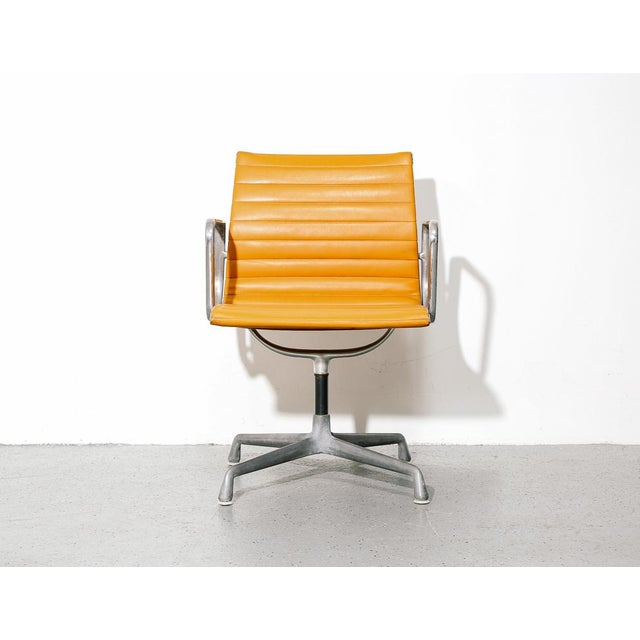 Eames for Herman Miller management chair. Orange naugahyde upholstery on aluminum frame and base. Stamped by the...