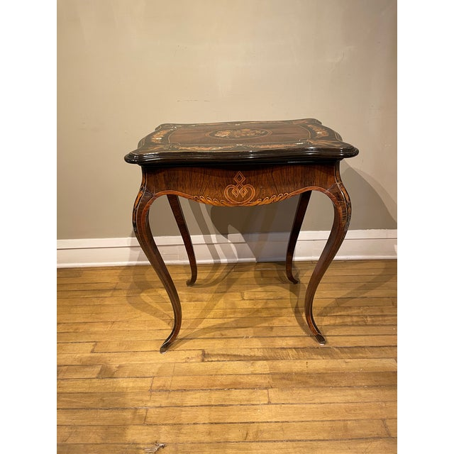This one of a kind burled walnut side table has an intricate floral, bird, ebonized, satinwood, and mother of pearl inlay....