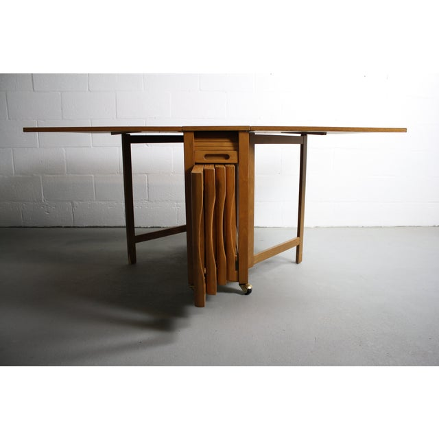 This is such a great find! It's a 1960's Mid Century Modern Drop Leaf Hide-A-Way Dining Table w/ 4 Folding Chairs made in...