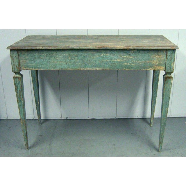 A high rectangular solid wood table with a worn paint surface.