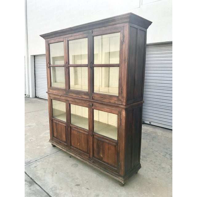 20th century brown-stained & antiqued vitrine with sliding glass and wood doors. According to original owner, it was...