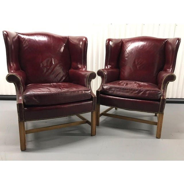 Amazing pair of leather wingback armchairs, circa 1970s. Leather is glossy-finished oxblood red. Brass tacks outline...
