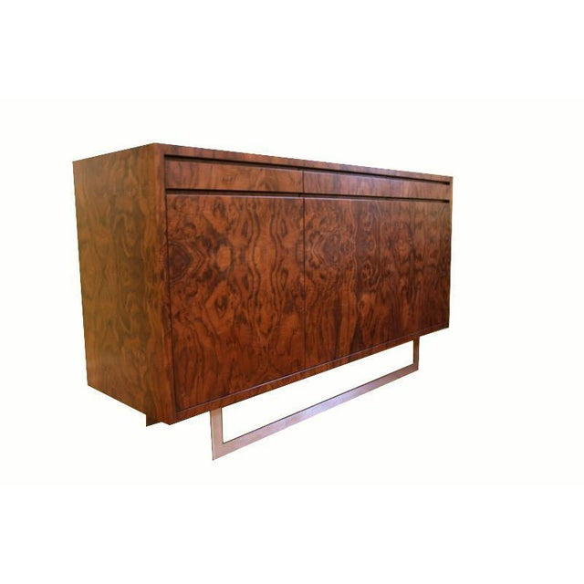 Mn Originals three-door walnut burl console on stainless base. Three small drawers on top with three doors below with...