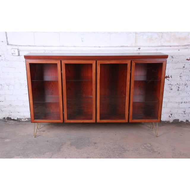 Offering an exceptional Danish rosewood glass front bookcase on hairpin legs by Skovby. The bookcase has four glass front...