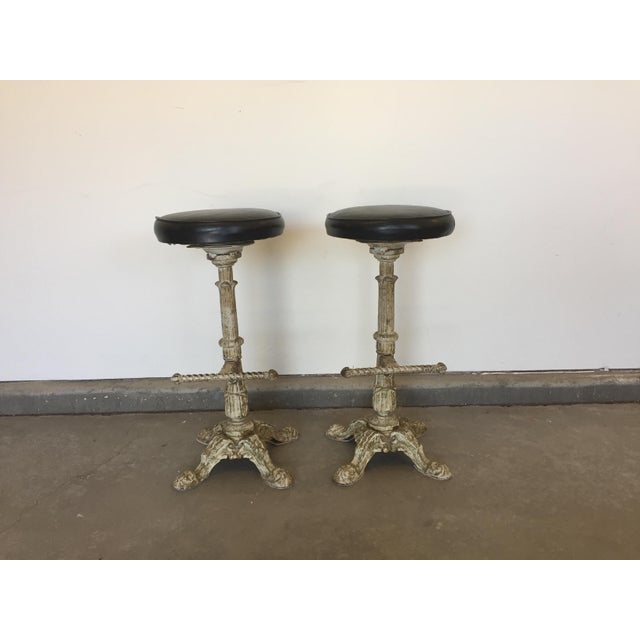 These antique barstools are cast iron and are painted in a distressed white with a black leather seat. The seat can be...