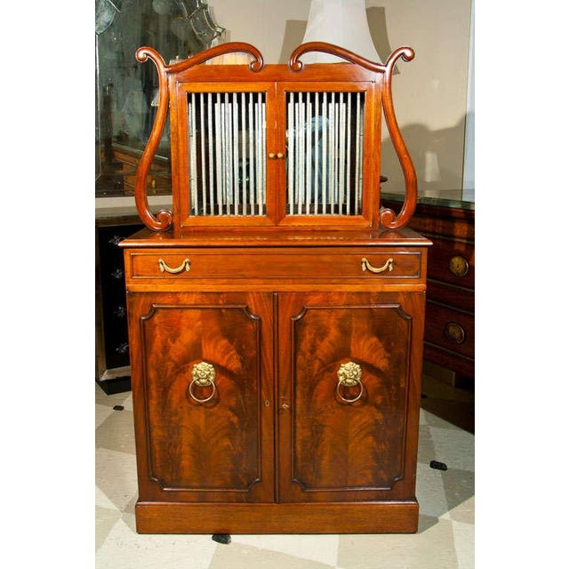 A fine quality mahogany liquor cabinet by Grosfeld House, circa 1940. The two-door cabinet with glass-rod decoration sits...