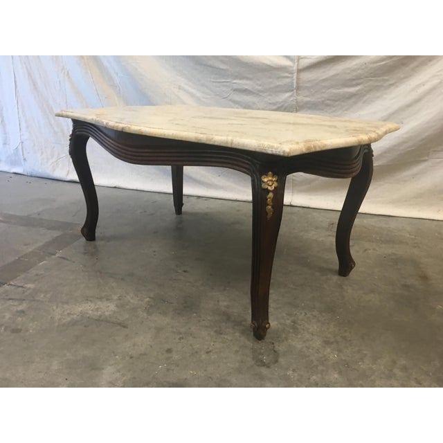 Beautiful Louis XV style marble top coffee table, with gilt floral accents. This lovely table is a timeless classic,...