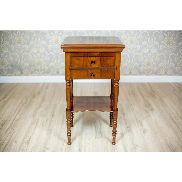 A piece of furniture on turned legs, with a liftable top and an extended desktop inside. Under the desktop, there are two...