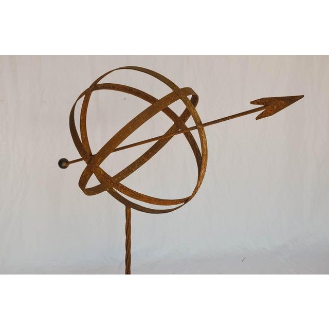 This armillary sphere is made of metal and has a rust color finish. It is mounted on a small concrete square. As a...