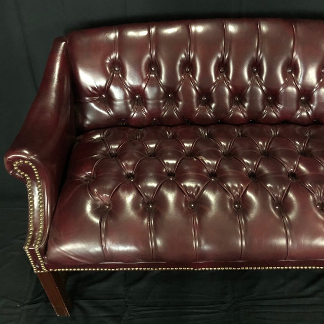 Diminutive Classic English burgundy leather Chesterfield bench or loveseat, with slightly arched back and rolled arms...