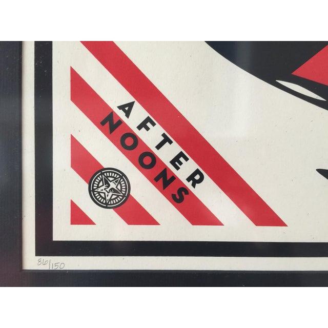 This original Shepard Fairey screen print is custom framed in a Nielsen matte black anodized metal frame. Both the foam...