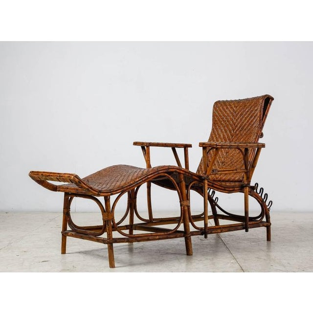 An adjustable chaise longue made of a bamboo and woven rattan. The backrest can be placed in four different positions. One...