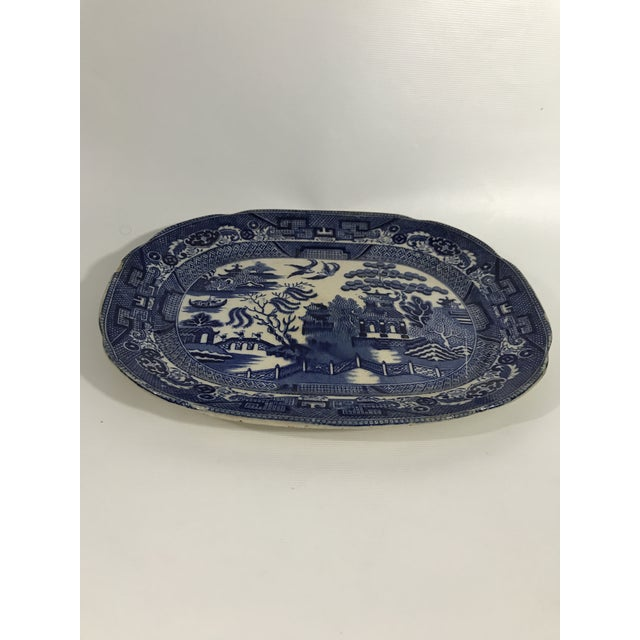 Antique oval blue and white porcelain serving platter with traditional blue willow transferware decoration.