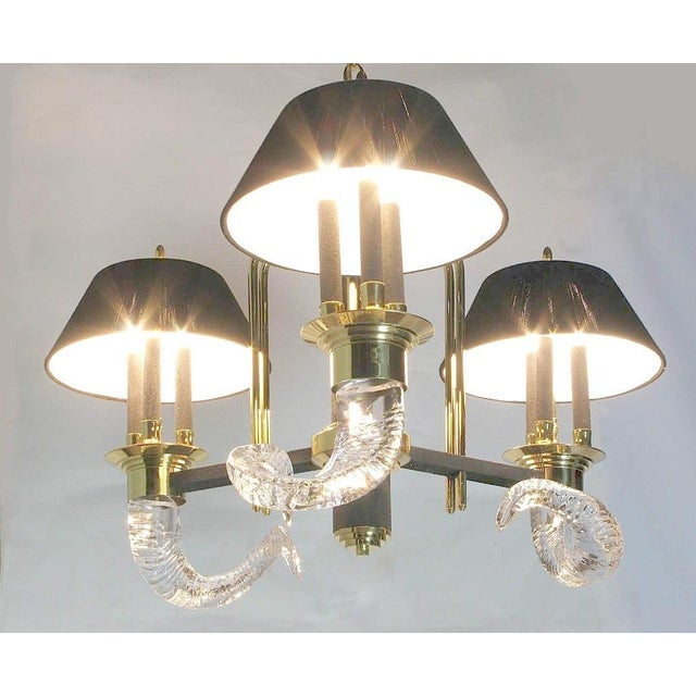 Unique and elegant, this three arm, nine light chandelier is a 1980s deco revival piece. Crystal rams' horns, solid brass,...